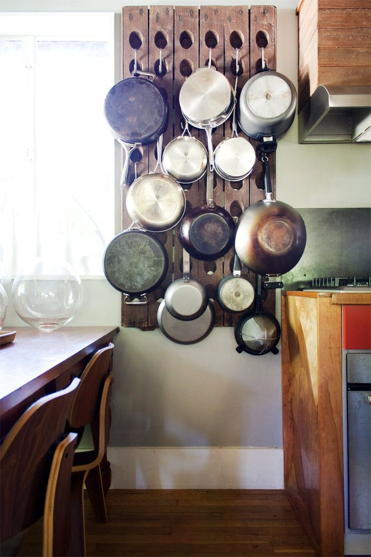 Briana and Dominic repurposed a French riddling rack to store pots and pans in their bungalow kitchen.