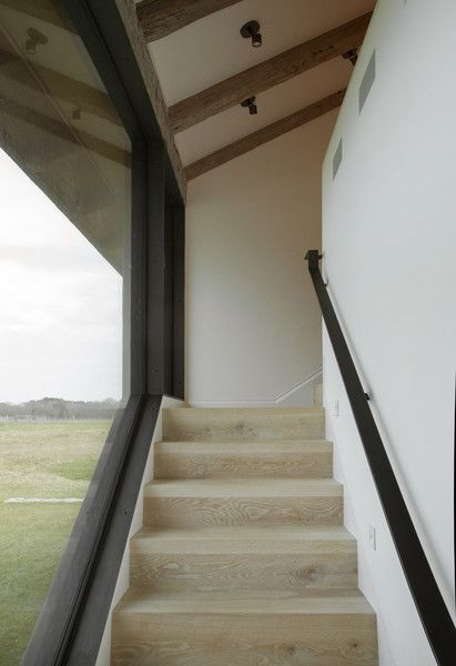 Contemporary Staircase: Large black framed window alongside wood stairway..
