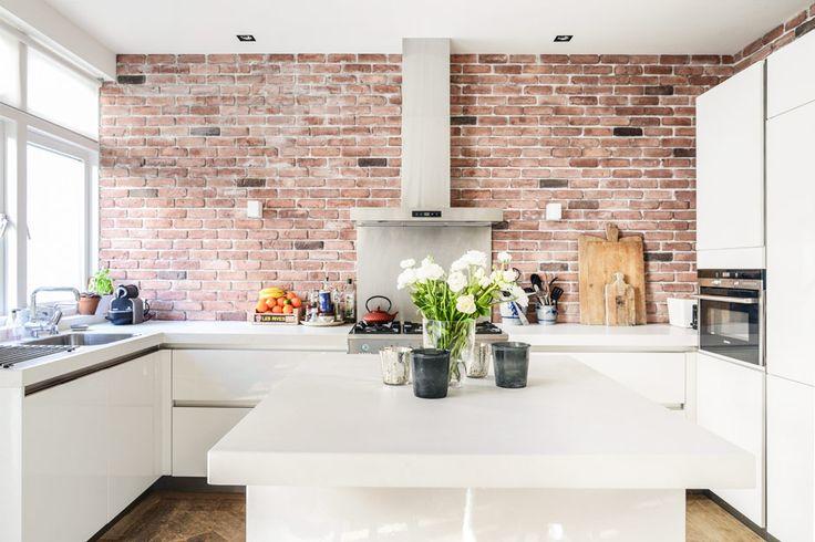Handleless white kitchen. Bare brick wall. Kid & Coe | The Brahmsstraat Residence | Amsterdam