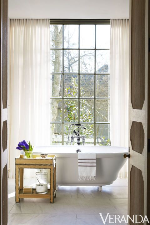 Brown and white paneleddoors open up to an airy bathroom with scenic views of Mountain Brook, Alabama. The tub is by Kohler, the fittings are by Lefroy Brooks, the side table is by Dransfield & Ross and the curtains are in a Classic Cloth fabric by Dessin Fournir.  Image originally appeared in the January/February 2016 issue of Veranda.   INTERIOR DESIGN BY LIZ HAND WOODS