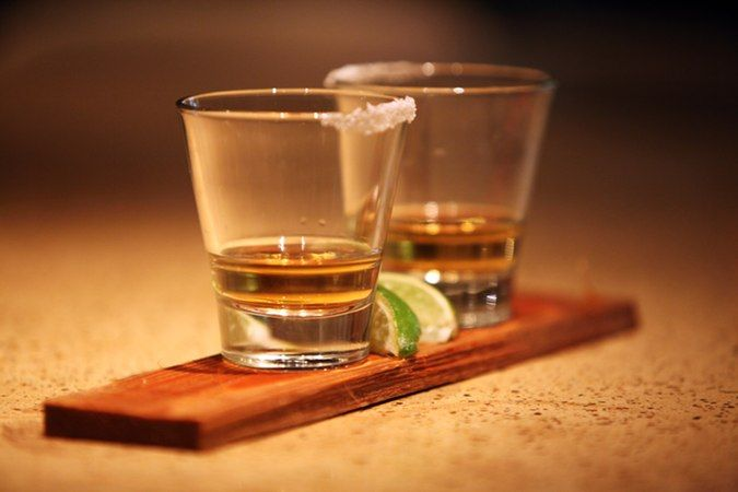 Two shot glasses of cedar wood-infused tequila at Smoke Restaurant in Dallas, which also serves maplewood-infused bourbon.