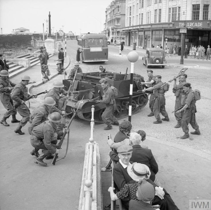 The townspeople of Worthing in Sussex watch with interest as the Home Guard resist an 'attack' on the pier by regular troops supported by a Universal carrier, 3 August 1941.