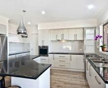 Kitchen features an angled island bench, matt white doors, black gloss laminate benchtops, and vinyl plank flooring.
