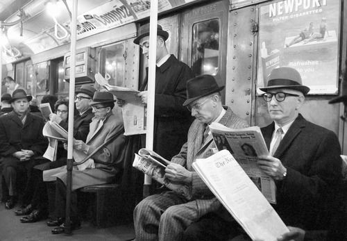 Riders read their morning newspapers after the end of the city's 114-day newspaper strike. New York, 1963.  By Jacob Harris