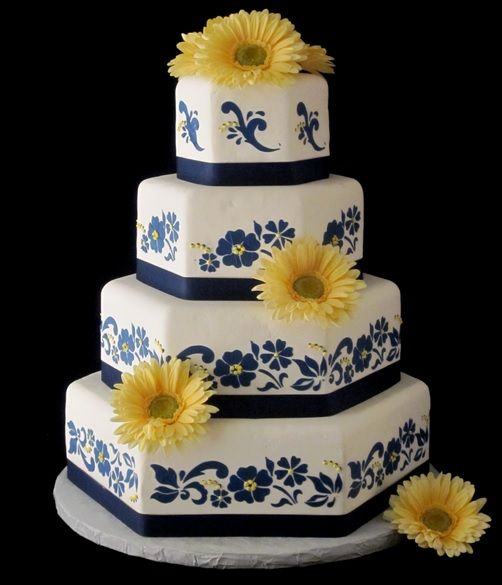 Navy & yellow gerber daisy wedding cake.  The Twisted Sifter Cake Shoppe. Bardstown, KY. Hexagon stacked cake in handmade marshmallow fondant.  The navy blue design is created in royal icing.  The cake is adorned with yellow gerber daisies. Stenciled blue flowers