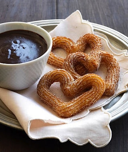 Spain's classic sweet street food comes stateside in this decadent recipe which features orange-flecked churro dough and a semisweet chocolate sauce with vanilla and cayenne pepper.