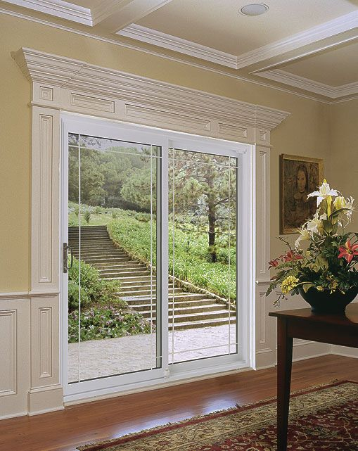 Idea for dressing up plain glass sliding doors - wood treatment around doors, and the frosting. I've also seen pics of DIY vinyl corner decals which can look good in place of the frosting [provided it doesn't clash with the moulding].