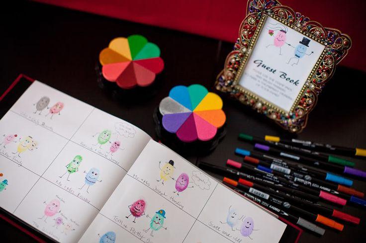 Un livre d'or où les invités doivent se dessiner en utilisant une empreinte de leur doigt et les crayons mis à leur disposition