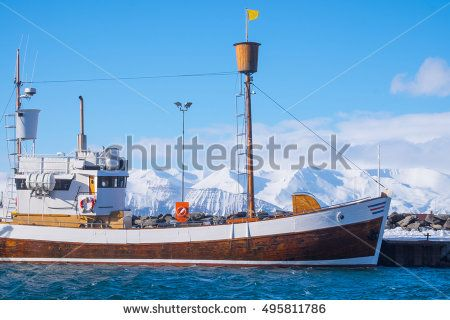 traditional old wooden fisherman boats lying in harbor in beautiful golden evening light at sunset, town of Husavik, Skjalfandi Bay, Iceland, northern Europe