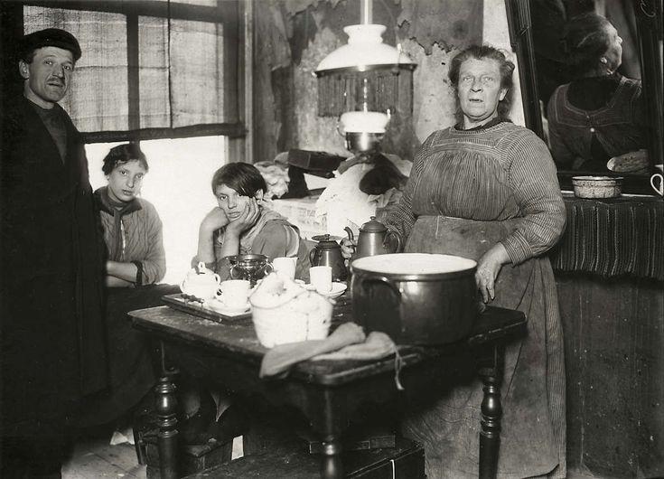 Gezin in vervallen en armoedige huiskamer van een krotwoning aan de Batavierstraat waar ze met 7 mensen wonen. De huur bedraagt vijf gulden. Nederland, Amsterdam, 1920.