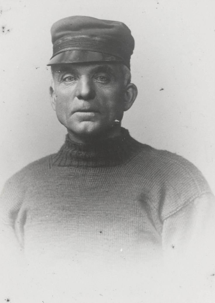 Schipper in streekdracht uit Bruinisse. De man draagt een donkerblauwe gebreide wollen visserstrui en een zwart lakense hoge pet met gladde zwarte klep. ca 1920 #SchouwenDuiveland #Zeeland
