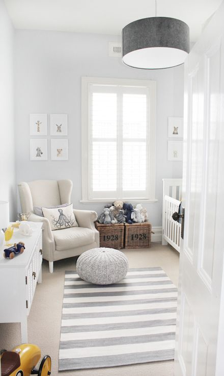 White and gray nursery features gray drum pendant, West Elm Short Drum Pendant, over white and gray stripe rug, CB2 Pull Up a Pouf on Crate & Barrel Olin Grey Rug, as well as linen slipcovered wingback glider accented with DL Rhein Embroidered Octopus Pillow next to numbered wicker baskets situated under window flanked by Sharon Montrose The Animal Print Shop Prints.
