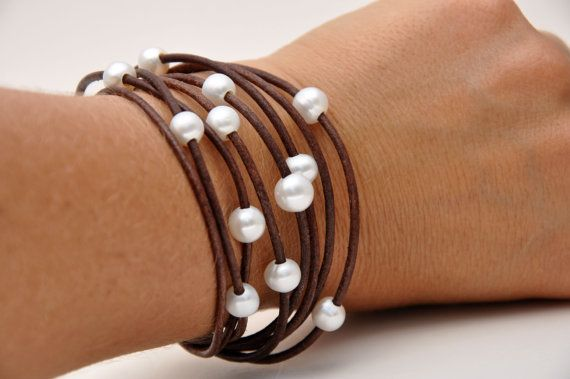 This is a beautiful Pearl and Leather Bracelet designed with 8 strands of 2mm medium brown leather and peppered with 10 / 8mm, 9mm - 10mm freshwater white pearls. It has a, newly designed, secure magnetic clasp made of solid stainless steel. The bracelet measures 7 3/8 inches. My wrist measures 6 1/2 inches, and it is a perfect fit. This Pearl and Leather Bracelet is a Must Have!  Perfect choice to start or add to your Pearl and Leather Jewelry Collection!  *Please note that the bracelet in…