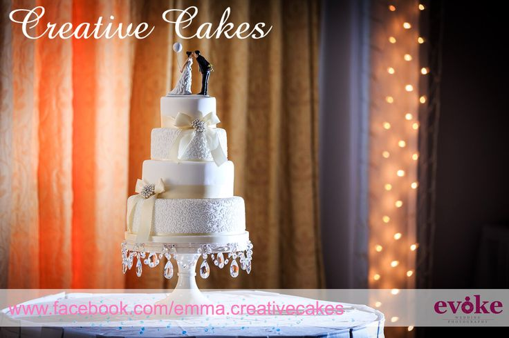 Simple white and cream wedding cake with hand piping, decorative satin ribbons and bows finished with a crystal and pearl brooch - design chosen by bride and handmade by Creative Cakes