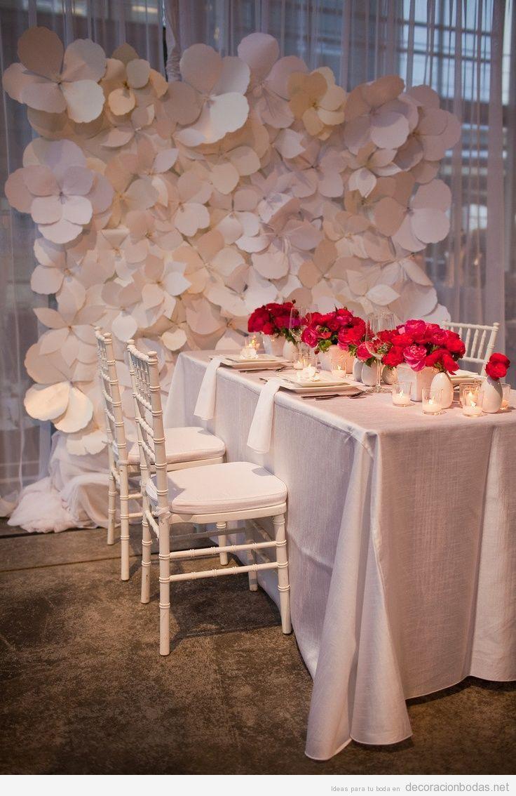 Pared de un salón de bodas decorada con flores blancas de papel