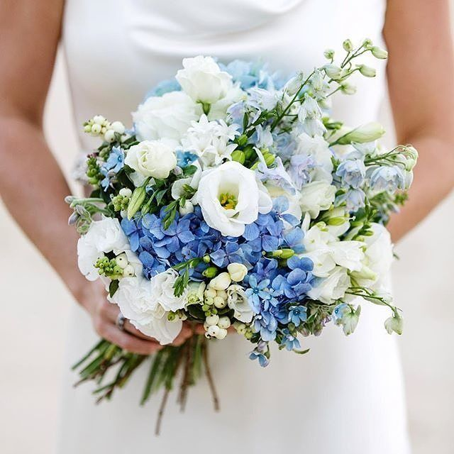 Beautiful Wedding Bouquet Featuring: White Lisianthus + Buds, White Freesia, White Hyacinth, White Snowberry, Blue Delphinium, Blue Hydrangea, Blue Tweedia, Greenery Foliage