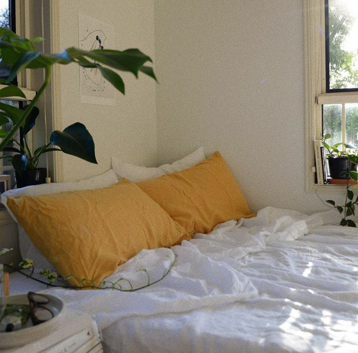 Spice up your minimalistic bedroom with burnt yellow pillows for a bohemian flare
