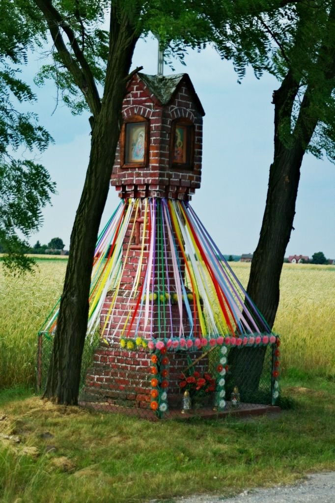 Wayside shrine in Poland. The custom of decorating them with colorful ribbons is an ancient Slavic practice predating the introduction of Christianity.