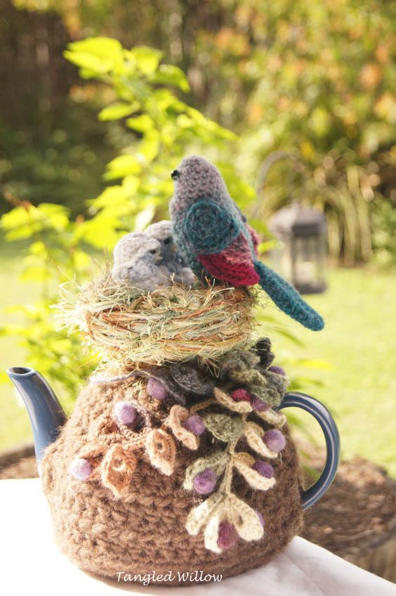 Three little birds nestle happily in a hand woven nest perched among foliage and pink and purple berries. This stunning Tea Cosy is a Tangled: