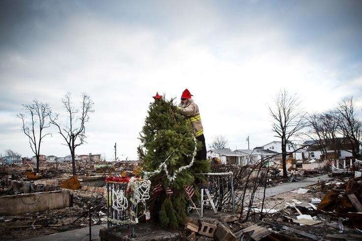 Een man tuigt een kerstboom op in een door storm Sandy getroffen wijk in Queens, New York.