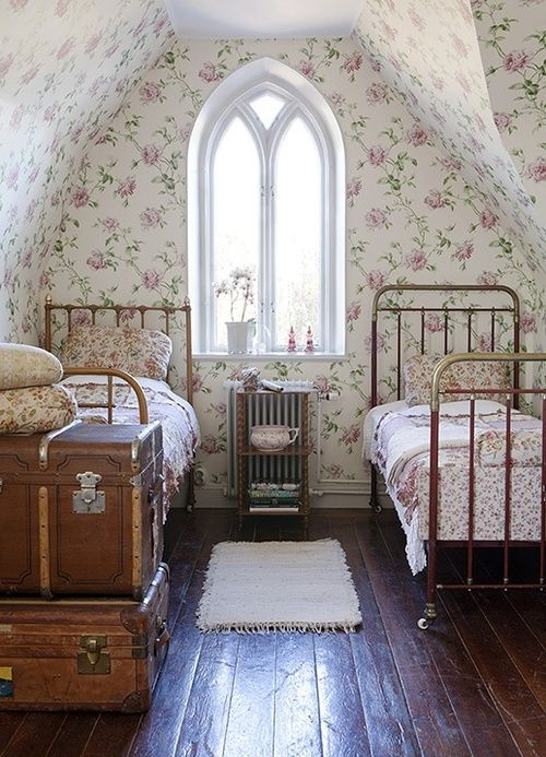 Oh my! - old trunks, brass beds, a beautiful window, wonderful wallpaper, and pretty bedding - all - on a lovely pitted old floor.