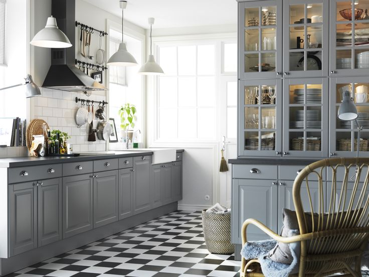 blue and gray with a checkerboard floor kitchen. Lots of window light. Subway tile. Glass door cabinets.