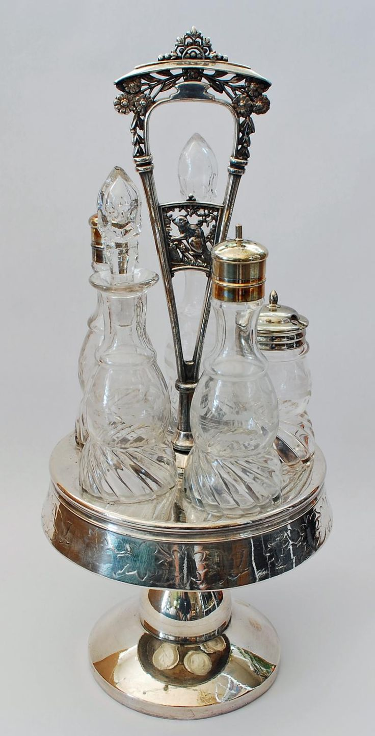 Silverplate and Glass Caster Set, circa 1880.  A caster set usually included salt and pepper shakers, a spice shaker, and cruets for oil and vinegar.