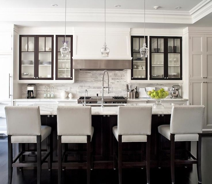 Gorgeous kitchen design with white kitchen cabinets, marble tiles backsplash, glass pendants, espresso kitchen island, marble counter tops, chrome faucet and hardware and white leather stools.