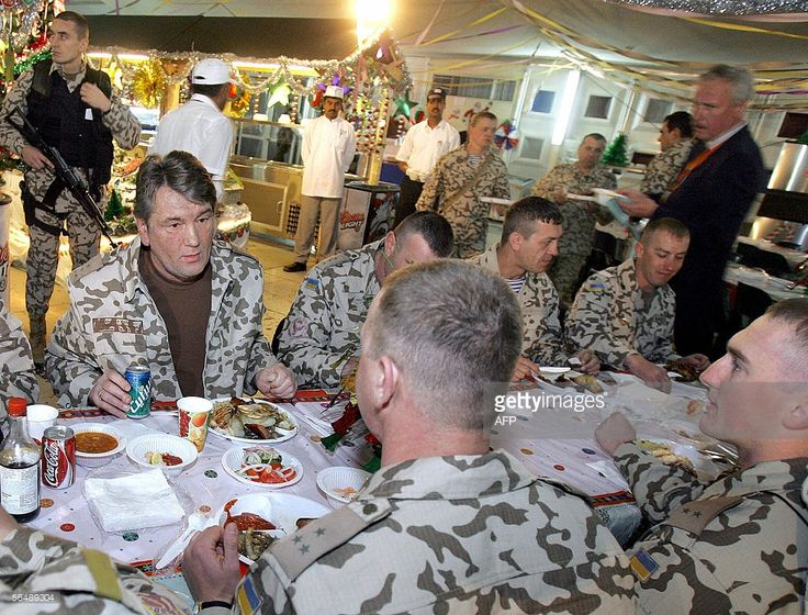 President of Ukraine Viktor Yushchenko (L) chats with officers during dinner at a military base near the Shiite city of Kut, where Ukrainian troops have been stationed, 26 December 2005. Ukraine President Viktor Yushchenko arrived in Iraq on Monday for a surprise visit, as Ukraine wrapped up a withdrawal of most of its troops from the country. Yushchenko ordered Ukraine's troops out of the country earlier this year after assuming power in the ex-Soviet country following last year's 'orange…