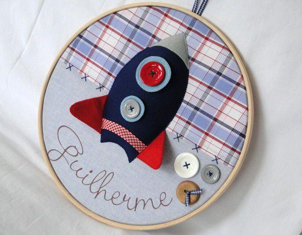 Quadro Porta Maternidade modelo Bastidor Foguetinho Espacial <br> <br>Confeccionado em tecido e feltro, decorado com botões plásticos e em madeira e personalizado com o nome do bebê. <br> <br>O quadro mede 30 cm de diâmetro e pode ser feito nas cores e estampas que desejar!