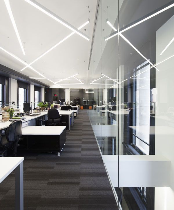 office lighting levels at work. classic regular office work space with meeting rooms adjacent to the open plan area desks. lighting levels at