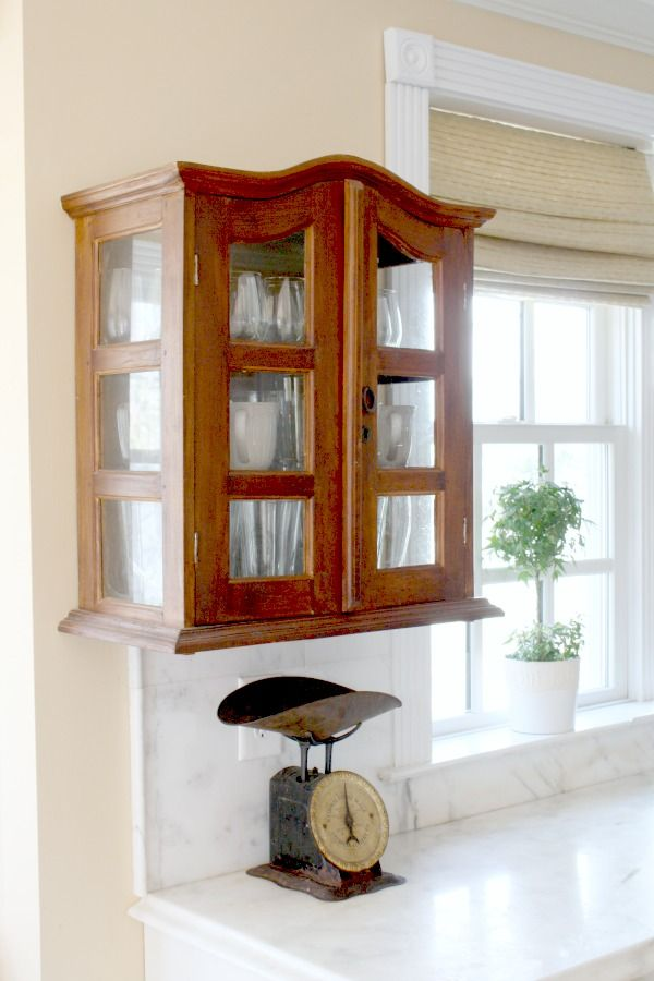The homeowners placed this vintage curio cabinet above the counter in their farmhouse kitchen. It gives the space character and charm, as well as a place to hold their cups and glassware.