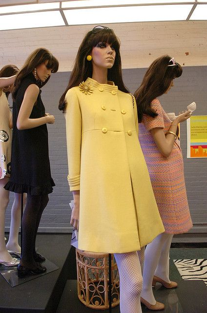 Yellow wool coat and dress by French couturier Andre Courreges. Styled in the look of Marlo Thomas in 'That Girl' with an enameled daisy brooch, cream tights, sunglasses worn as a headband, and a pair of gloves being carried...not worn. Chain handle quilted handbag and black flat patent leather shoes.
