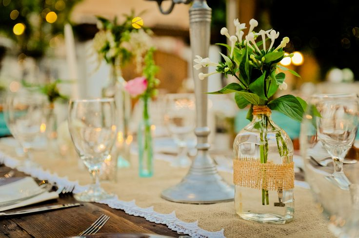 centerpieces using old bottles at a vintage wedding / like burlap and twine on bottles