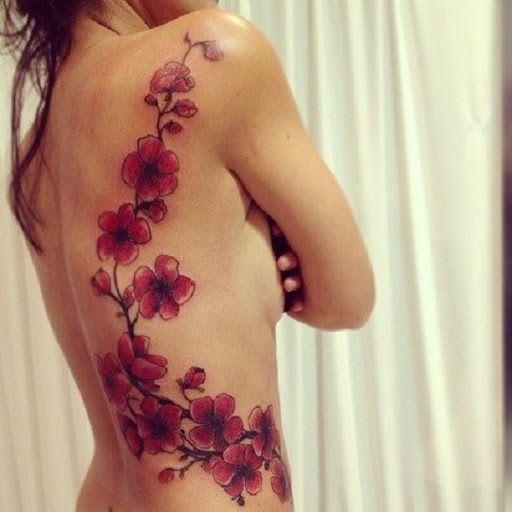 Uma bela cadeia de flores de cerejeira em tatuagem. As flores de cerejeira estão lindamente coloridas em tons de vermelho, enquanto os ramos lentamente fina e quase desaparece dando a ilusão de que as flores de cerejeira são magicamente para cima, agarrando-se a pessoa de volta. (Foto: Fontes de imagem)