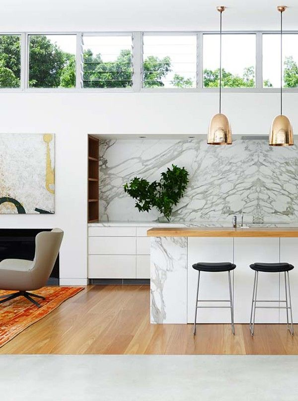 Modern kitchen featuring dramatic marble backsplash, wooden countertops and hardwood floors, mod gold lighting and simple white cabinets | Arent & Pyke