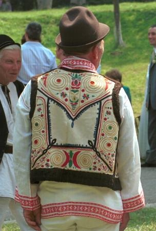 Romanian costume Dobroteşti - Dolj  Short fabric waistcoat called giubea, edged with fur worn by a pipemaker. Decorated with red, yellow and green embroidery. The 'squirl' patterns are typical of this area of southern Romania. Brown 'trilby' shaped felt hat   Photo taken at Astra Museum, Sibiu, August 1998