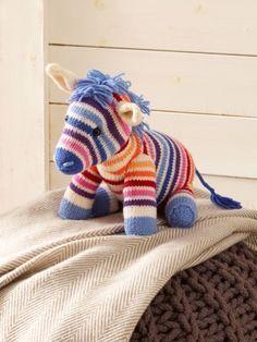 Regenbogen-Zebra Nora sucht ein neues Zuhause. Folgen Sie einfach unserer Strickanleitung und schon bald kann das Stricktierchen bei Ihnen einziehen.