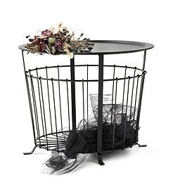 A storage table in black powder coated steel with airy storage under the table top.