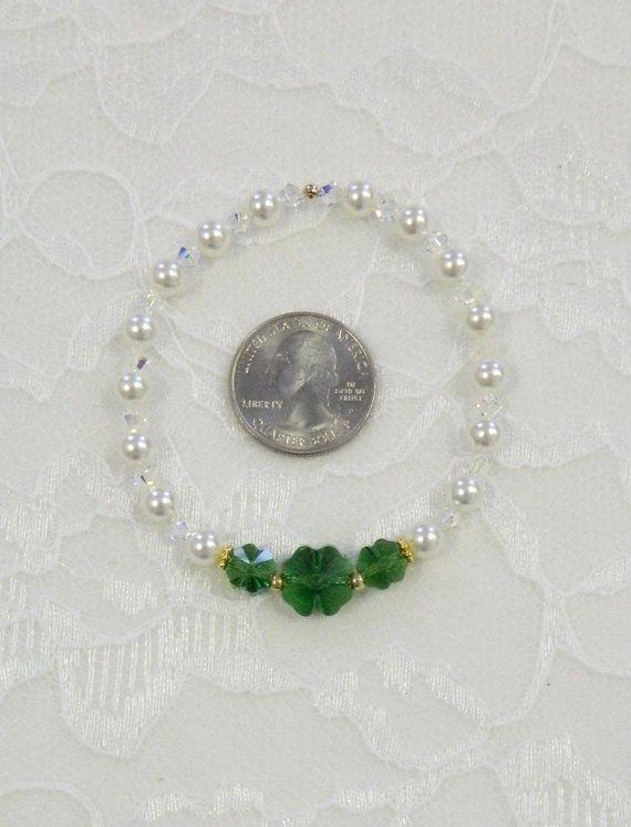 Todo el mundo es irlandés el día de St. Patrick!  Esta bonita pulsera de ESTIRAMIENTO se hace con 2 de 8mm y 1 mm 12 genuino Swarovski oscuro verde musgo cristal tréboles. También utilizar espaciador de Daisy y oro galvanizado Rocallas 8/0 como acentos y alternan perlas de blanco Swarovski 6mm y 4mm bicones cristal AB y había asegurado con funda y tubo de presión lleno de oro de 14 K.  La pulsera mide 7 1/2 pulgadas de largo y deben caber a cualquier persona que necesite de 7 a 8 pu...