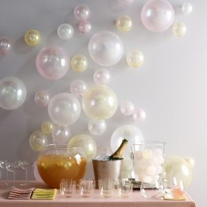 A bubbly backdrop can be created by filling clear balloons with iridescent colored glitter.