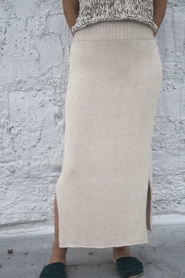 Long cotton cream skirt with ribbed and elastic waist and side slits.