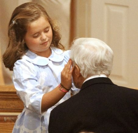 Carolina Shriver, left, granddaughter of Sargent Shriver, right, touches his face during a wake for Eunice Kennedy Shriver at Our Lady of Victory Roman Catholic Church, in the Centerville section of Barnstable Thursday. Eunice Shriver, the sister of President John F. Kennedy and Sen. Edward M. Kennedy, died at Cape Cod Hospital at age 88.