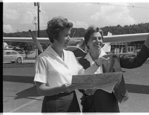 Joan Mace and another pilot point while holding aviation chart at the old Ohio University airport, 1969 :: Ohio University Archives