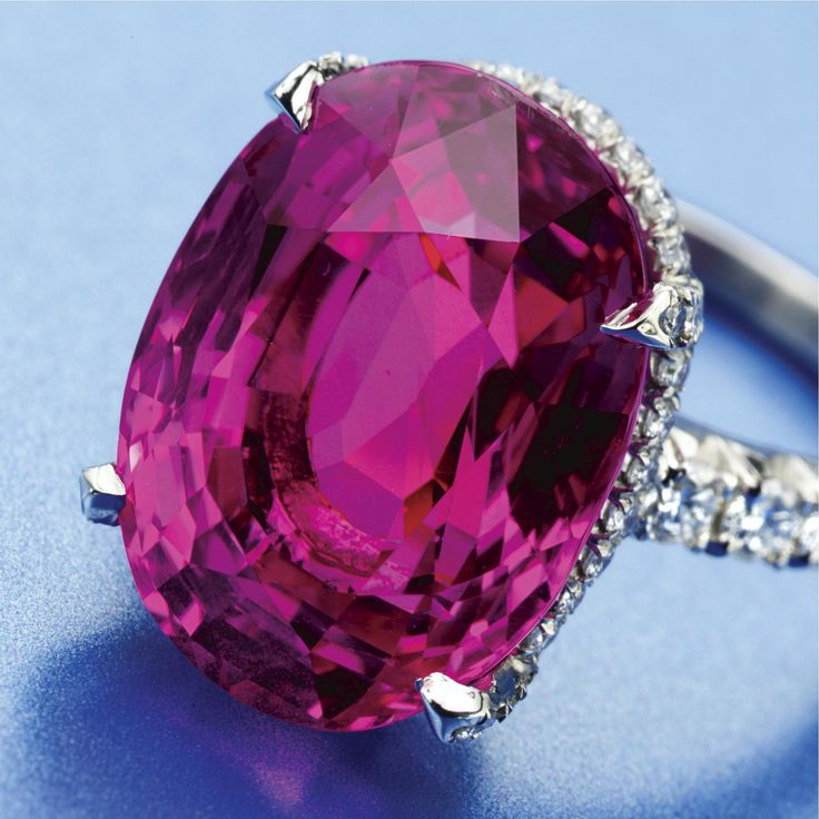 PINK SAPPHIRE AND DIAMOND RING The oval sapphire weighing 17.16 carats, bordered by numerous round diamonds weighing approximately 1.15 carats, mounted in platinum