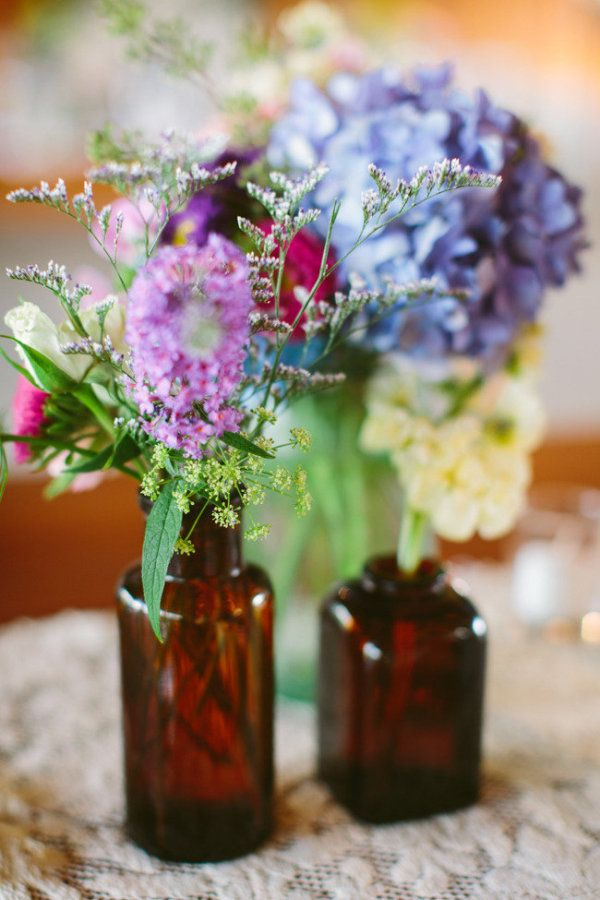 Cheap and cheerful table decorations. You can find some small bottles of various shapes, colours and sizes in most craft stores. Then you can put a few individual blooms in each one. The place a dozen or so on each table for an effective display.