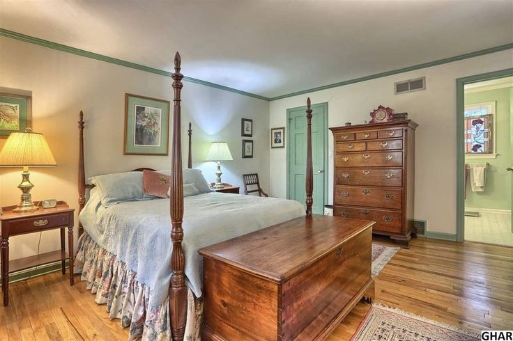Die warmen Töne, Spill über das Himmelbett, Fußboden- und hölzernen Befestigungen machen dieses Master-Schlafzimmer aussehen, rustikal und gemütlich.