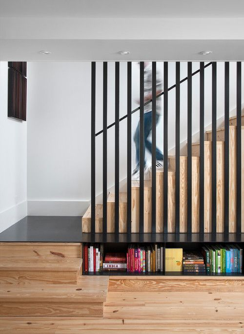 A steel landing in this home turns into a bench with book storage below.