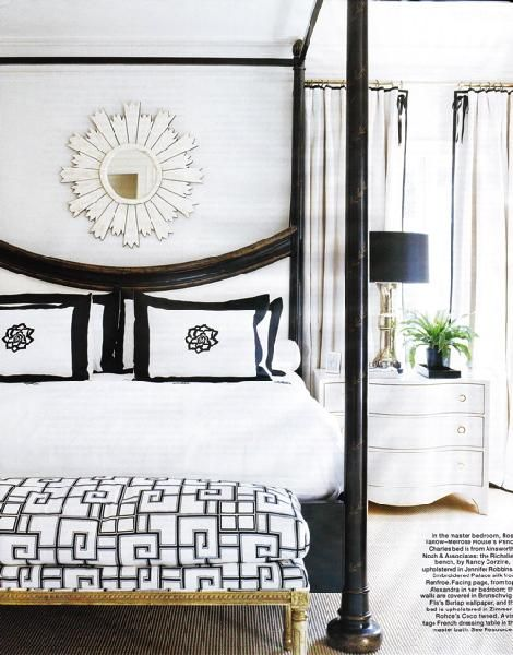 Modern white & black bedroom design. Glossy black canopy bed with white lacquer sunburst starburst mirror! Love the whitewashed nightstand chest and black lamps! White chic modern bedroom. White paint wall color! Black white gold silver bedroom colors.