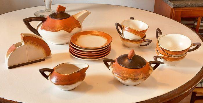 Een fraai 10-delig Art Deco theeservies, in de kleuren oranje bruin en beige. Het theeservies bestaat uit een theepot een suiker potje eenen melkkannetje. een servet houder en 6 kop en schotels.  Gemerkt: Dek. 6  Conditie is zeer goed  Afmetingen:  -- Theepot -- Ca. 15 cm hoog x 28 cm breed -- Suikerpotje -- Ca. 10 cm hoog  x 14 cm breed --  Melkkannetje -- Ca. 5 cm hoog x 13 cm breed -- Servethouder -- Ca. 15 cm x 10 cm hoog -- Kopje -- Ca. 5 cm hoog x 14 cm breed  -- Schotels --  Ca. 16…